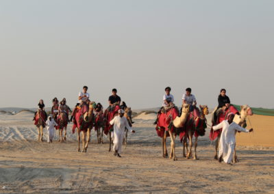 students riding camels through the desert