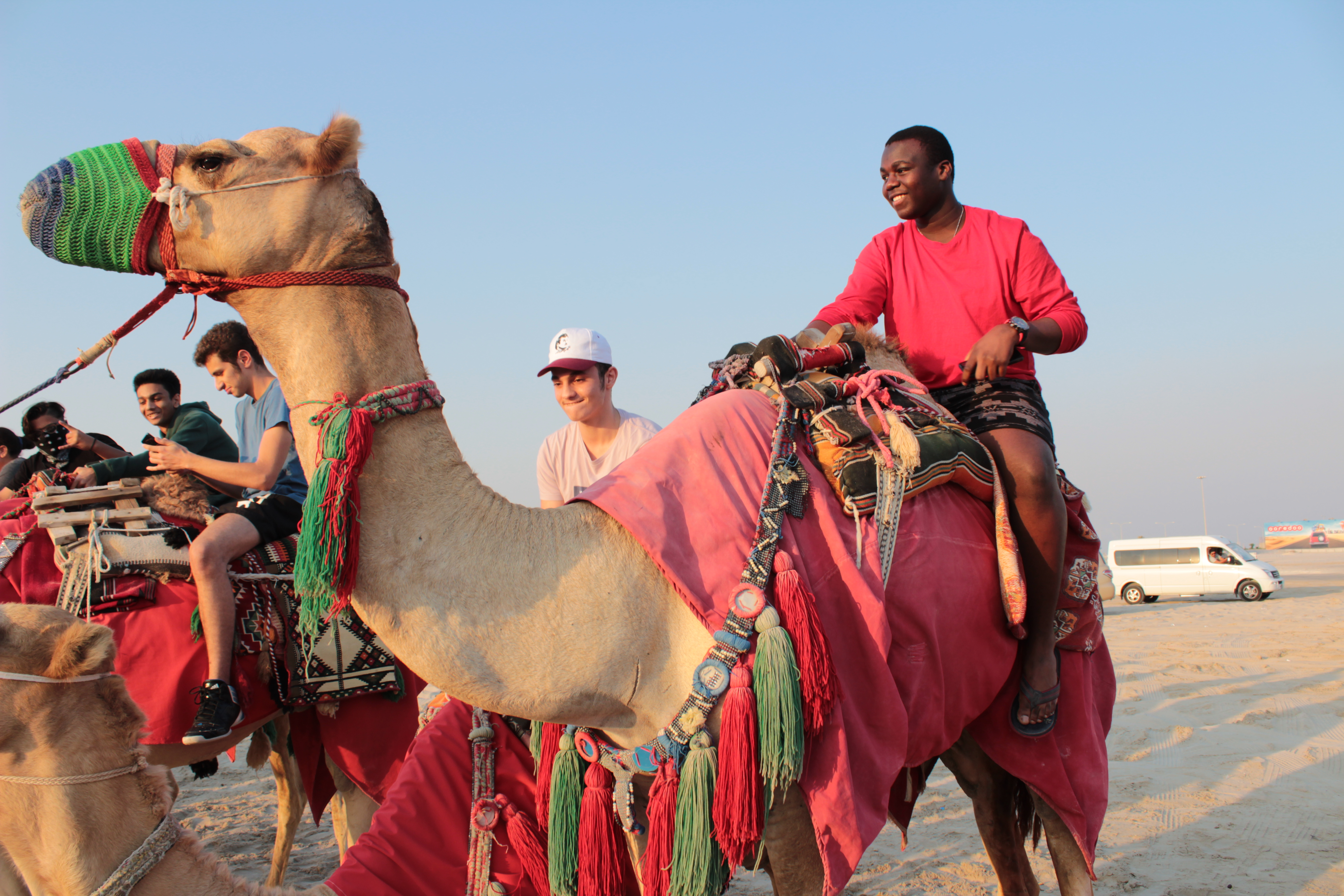student smiling on the back of a camel