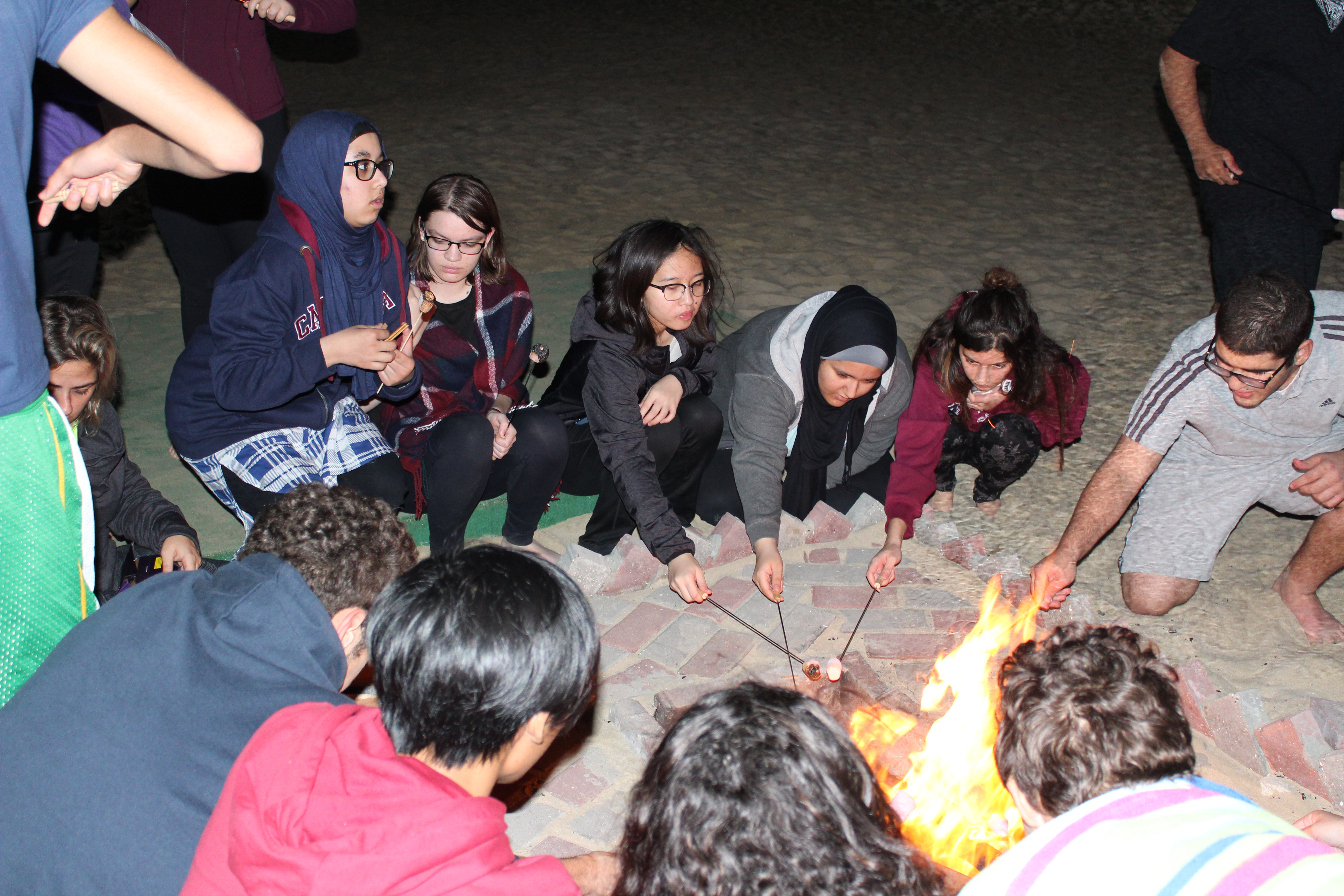 students roasting marshmallows over the fire