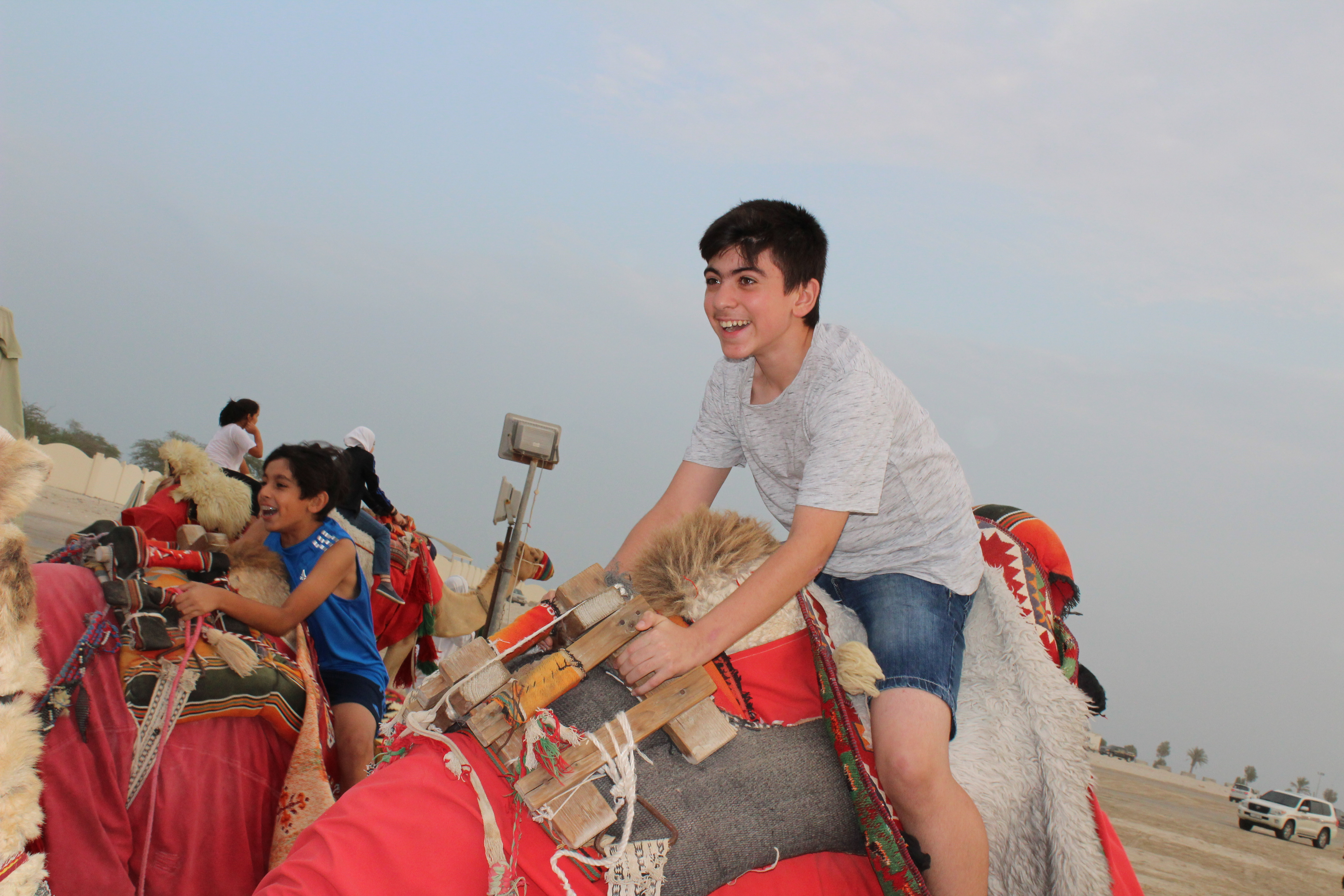 students laughing on back of camel