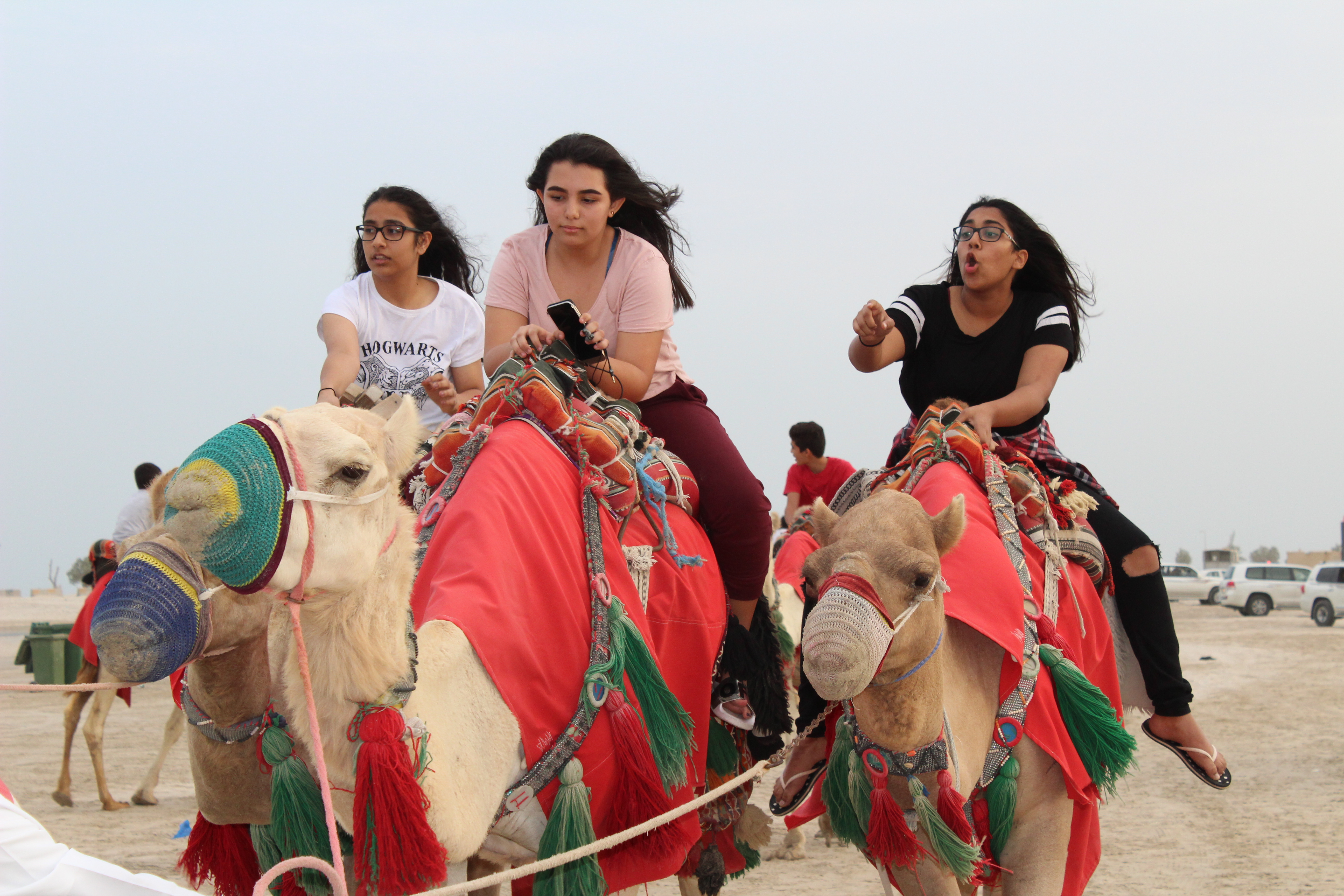 3 female students riding camels