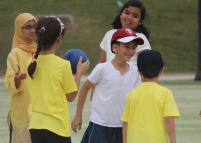students smiling and playing hand ball