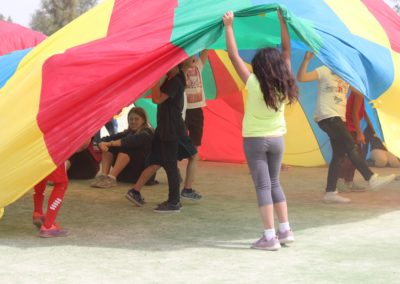 students playing with rainbow tent
