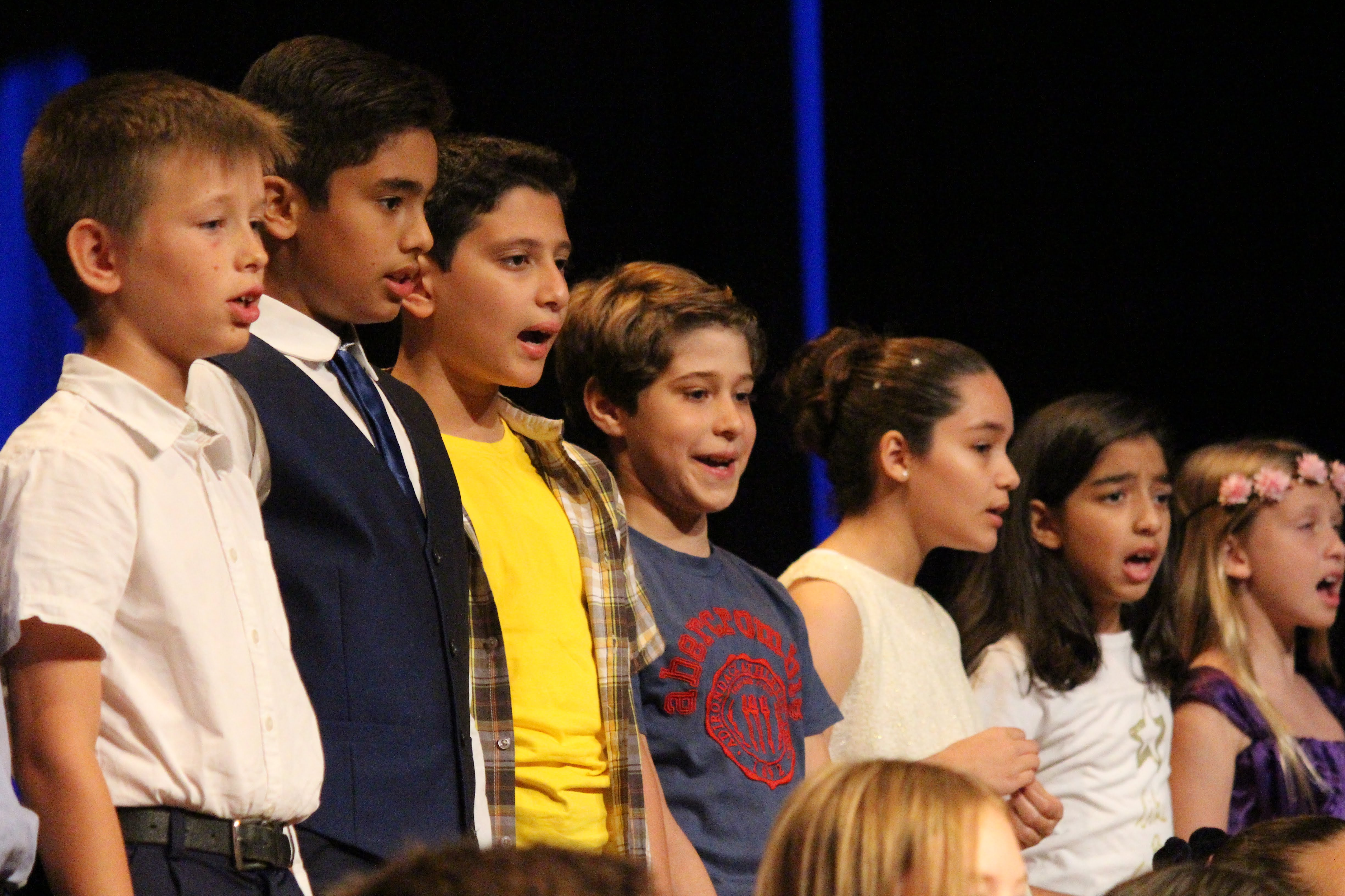 students on stage singing at spring concert